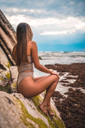 A dark-haired caucasian woman in a brown swimsuit on a natural background next to rocks and sea in the town of Zumaia, Gipuzkoa. Basque Country. In the summer sunset. Sitting facing away from the sea
