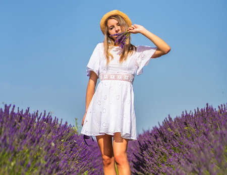 Rural lifestyle, young blonde caucasian woman in white dress and straw hat in a lavender field with her purple flower in Olite. Navarra, Spain. Smelling the flowers