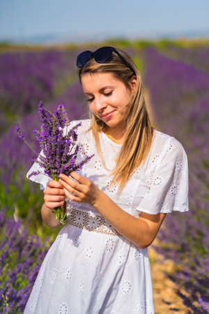 Rural lifestyle, Caucasian young blonde woman in white dress and sunglasses in a lavender field with her purple flower in Olite. Navarra, Spain. With a bouquet of flowers in hand