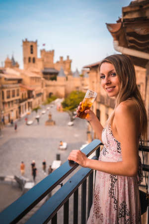 Young blonde caucasian woman in a long pink dress enjoying a beautiful rural in the town of Olite in Navarra.