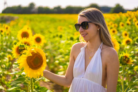 A blonde Caucasian woman with sunglasses and a white dress in a beautiful field of sunflowers on a summer afternoon, rural lifestyle. Navarra, Spain. Enjoying the flowers