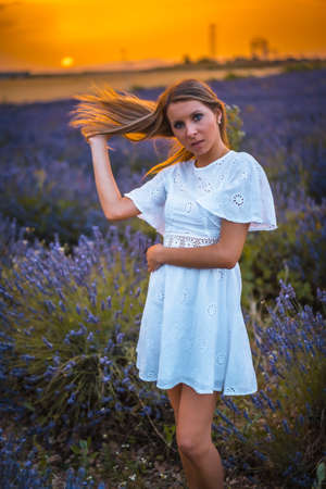 A young blonde Caucasian woman in a white dress in a cultivated lavender field in Navarra, Spain. lifestyle, rural lifestyle in purple lavender flowers at sunset