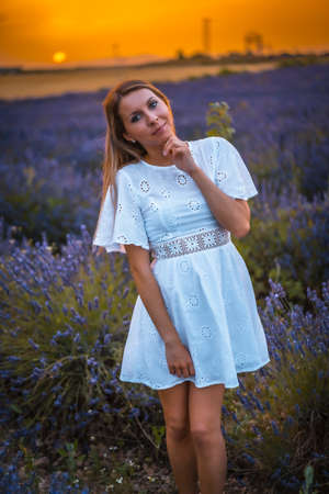 A young blonde Caucasian woman in a white dress in a cultivated lavender field in Navarra, Spain. lifestyle, rural lifestyle in purple flowers at sunset Foto de archivo