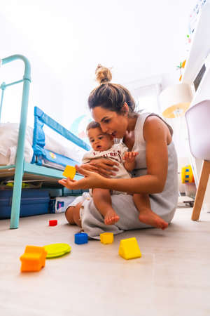 Young Caucasian mother playing with her in the room with toys. Baby less than a year learning the first lessons of her mother. Mother playing with her son and hugging him lovingly
