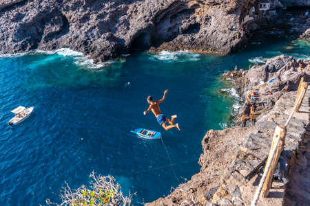 A young man making a very high jump into the water in the town of Poris de Candelaria on the north-west coast of the island of La Palma, Canary Islands. Spain. Pirate town
