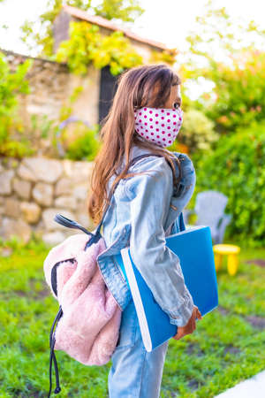 Caucasian girl with face mask ready to go back to school. New normality, social distance, coronavirus pandemic, covid-19. Jacket, backpack, mask with pink dots and a blue block in hand Stock Photo