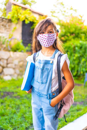 Caucasian girl with face mask ready to go back to school. New normality, social distance, coronavirus pandemic, covid-19. Jacket, backpack and a blue block for notes in hand