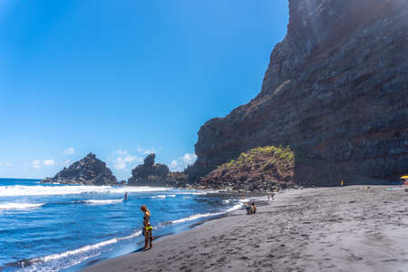 A young tourist enjoying summer by the sea on some rocks in Playa de Nogales in the east of the Island of La Plama, Canary Islands. Spain Stock Photo