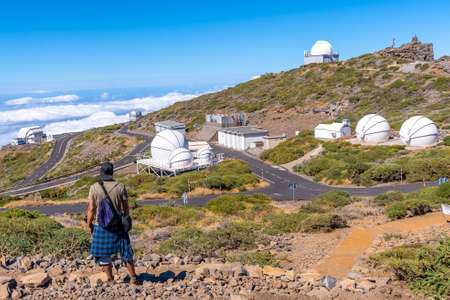 A young man on the trail looking at the telescopes of the Roque de los Muchachos national park on top of the Caldera de Taburiente, La Palma, Canary Islands. Spain