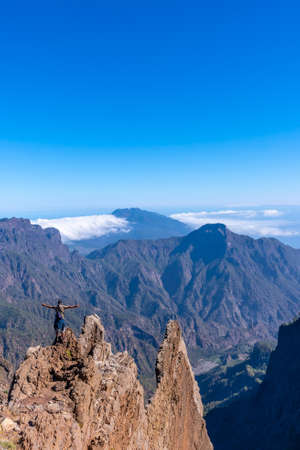 A young man after finishing the trek at the top of the volcano of Caldera de Taburiente near Roque de los Muchachos looking at the incredible landscape, La Palma, Canary Islands. Spain