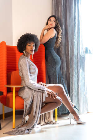 Fashion editorial, two friends in evening dresses sitting on a red sofa at a private party in a hotel, lifestyle. Glamor lifestyle, exclusive party. Blonde girl and brunette girl with afro