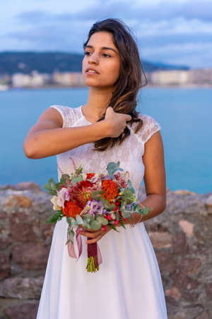 Portrait of young caucasian girl in white wedding dress on her wedding day by the sea