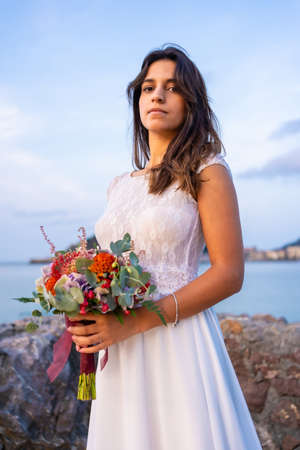 Caucasian brunette in white wedding dress, with a beautiful bouquet of flowers by the sea