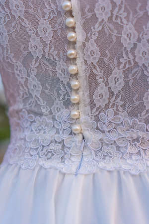 Lifestyle, detail of the seam texture of the bride's beautiful white dress. Caucasian brunette on her wedding day