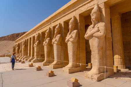 A young woman with pharaoh sculptures entering Hatshepsut's Funerary Temple in Luxor. Egypt Banco de Imagens