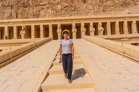 A young woman on the entrance stairs to the Funerary Temple of Hatshepsut in Luxor. Egypt