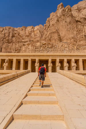 A young woman visiting the Mortuary Temple of Hatshepsut without people on her return from tourism in Luxor after the coronavirua pandemic, Egypt