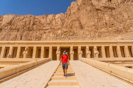 A young man with a face mask visiting the Mortuary Temple of Hatshepsut in Luxor after the return from tourism to Egypt Banco de Imagens