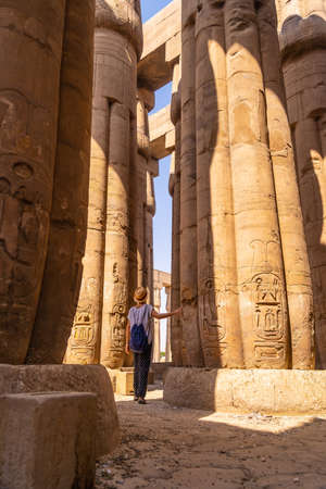 A young tourist in a white t-shirt and hat looking at ancient egyptian drawings on the columns of the Temple of Luxor, Egypt