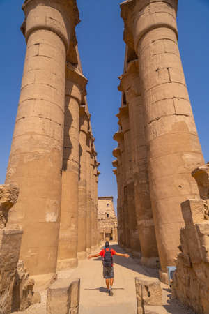 A young tourist next to the precious columns with Egyptian drawings in the Temple of Luxor, Egypt 版權商用圖片 - 157570681