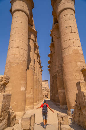 A young tourist next to the precious columns with Egyptian drawings in the Temple of Luxor, Egypt 版權商用圖片 - 157570683