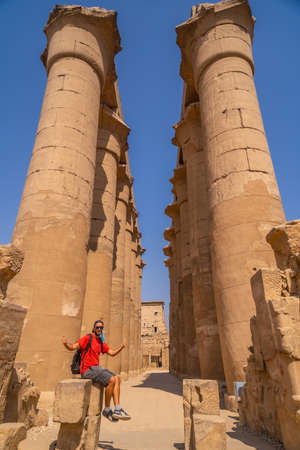 A young tourist next to the precious columns with Egyptian drawings in the Temple of Luxor, Egypt