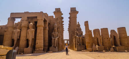 A young tourist with a hat visiting the Egyptian Temple of Luxor and its beautiful columns. Egypt