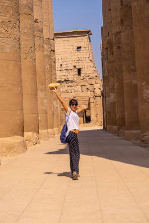 A young tourist with a hat visiting the Egyptian Temple of Luxor and its beautiful columns. Egypt 版權商用圖片 - 157594243