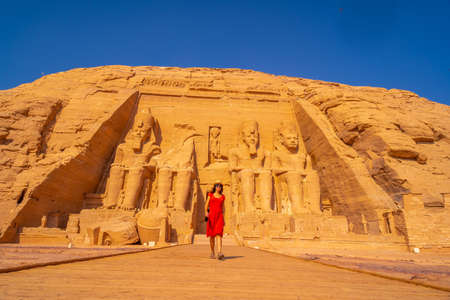 A young tourist in a red dress leaving the Abu Simbel Temple in southern Egypt in Nubia next to Lake Nasser. Temple of Pharaoh Ramses II