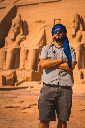 A young tourist with a blue turban visiting the Abu Simbel Temple in southern Egypt in Nubia next to Lake Nasser, the pharaohs in the background. Temple of Pharaoh Ramses II, travel lifestyle
