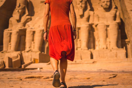 A European tourist in red dress walking towards the Abu Simbel Temple in southern Egypt in Nubia next to Lake Nasser. Temple of Pharaoh Ramses II, travel lifestyle