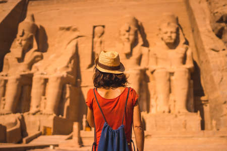 A young tourist in a red dress and straw hat walking towards the Abu Simbel Temple in southern Egypt in Nubia next to Lake Nasser. Temple of Pharaoh Ramses II, travel lifestyle