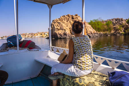 A young woman traveling by boat on the River Nile to the Philae temple dedicated to Isis, goddess of love. Aswan. Egyptian