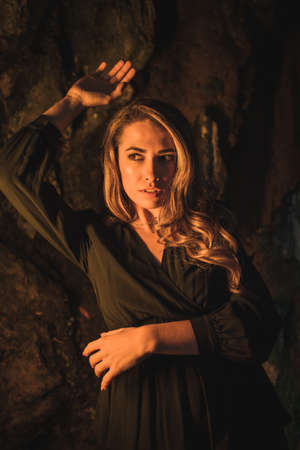 Lifestyle, a young Caucasian blonde in a black dress in a photo inside a cave, illuminated with yellow light. Very seductive pose of the model