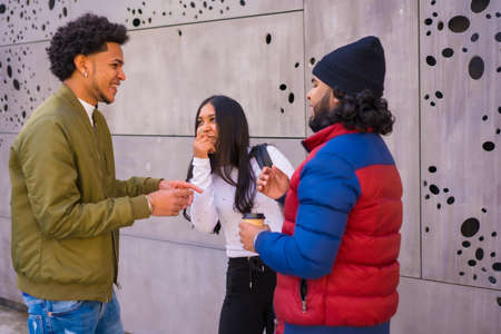 Urban style, three black Latino friends having fun in the street and talking to each other. Afro hair boy, brunette boy with long hair with hat Stock Photo