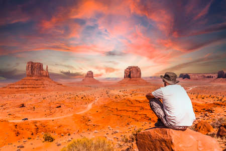 A young man in a white t-shirt in Monument Valley National Park at the visitor center at sunset, Utah. United States