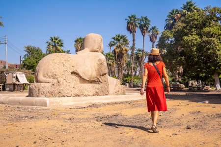 A young tourist in a red dress visiting the beautiful Sphinx of Memphis in Cairo, Egypt. Ancient city in which the god Ptah was worshiped