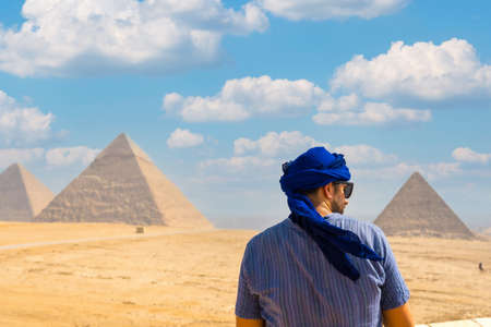 A young tourist wearing blue turban and sunglasses enjoying the Pyramids of Giza, the oldest Funerary monument in the world. In the city of Cairo, Egypt
