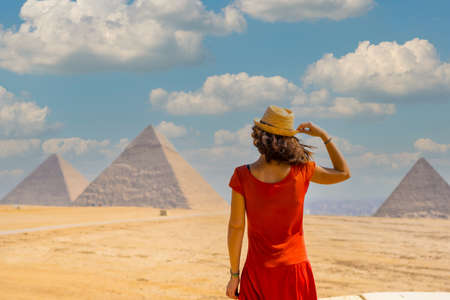 A young tourist in a red dress looking at the Pyramids of Giza, the oldest Funerary monument in the world. In the city of Cairo, Egypt 版權商用圖片