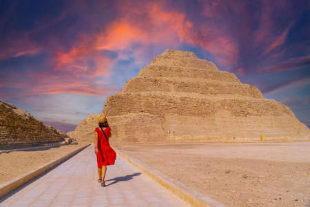 A young tourist in a red dress at the Stepped Pyramid of Djoser at sunset, Saqqara. Egypt. The most important necropolis in Memphis. The first pyramid in the world