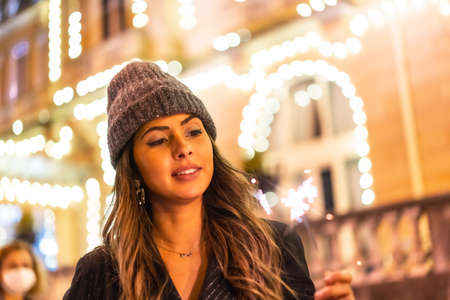 Christmas portrait with christmas lights in a beautiful building in the city, young caucasian woman at night with some torches in hand. With a winter hat
