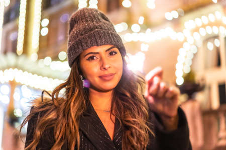 Christmas with Christmas lights in a beautiful building in the city, Caucasian young woman at night with some torches with fire in hand