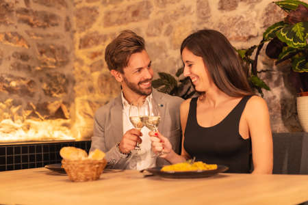 Lifestyle, a young European couple having dinner in a beautiful restaurant, celebrating Valentine's Day