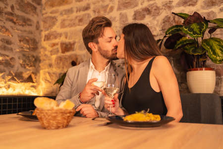 Lifestyle, a young couple in love kissing in a restaurant, having fun having dinner together with food, celebrating Valentine's