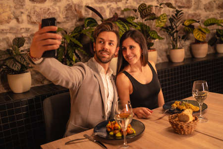 Lifestyle, a young couple in love in a restaurant, having fun dining together, celebrating Valentine's Day, taking a souvenir selfie