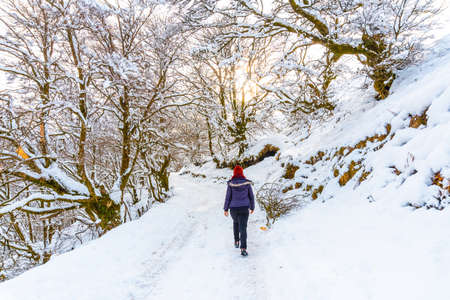 A young woman walking through the snow in the snow-covered Oianleku natural park in the town of Oiartzun, next to Peñas de Aya in winter, Gipuzkoa. Basque Country