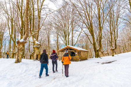 Young people visiting the snow-covered Oianleku natural park in the town of Oiartzun, next to Peñas de Aya in winter, Gipuzkoa. Basque Country