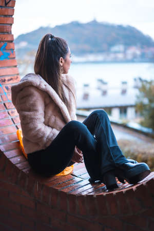 Caucasian brunette model sitting in winter looking at the city. Street style fashion Standard-Bild