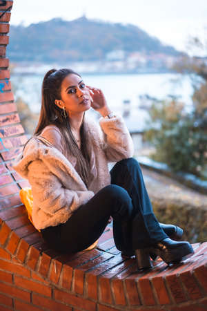 Caucasian brunette model sitting in winter with city in background. Street style fashion Standard-Bild