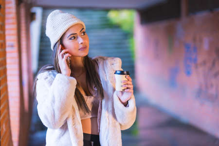 Young pretty Caucasian brunette in the city making a call with the phone, wearing a pink wool sweater and hat. Street style fashion